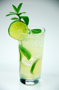 Mojito made with rum, lime, sugar, mint, club soda, served in a tall glass.